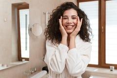 逗人喜爱的妇女在卫生间里照料她的皮肤 库存照片