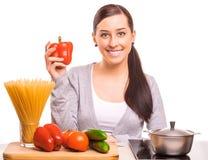 逗人喜爱的妇女在厨房烹调 免版税库存照片