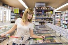 逗人喜爱的妇女在超级市场选择冻产品 免版税库存照片