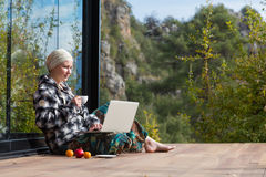 逗人喜爱的妇女坐木客舱大阳台与膝上型计算机和咖啡的 库存图片