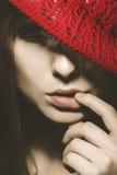 逗人喜爱的妇女垂直的画象有红色帽子和手指的在嘴唇附近 库存照片