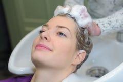 逗人喜爱的妇女安排头发洗在沙龙 库存图片