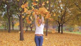 逗人喜爱的妇女投掷的秋叶获得笑的乐趣在五颜六色的森林叶子 影视素材