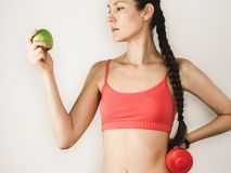 逗人喜爱的妇女用在训练期间的苹果与哑铃 免版税库存图片