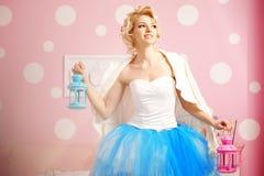 逗人喜爱的妇女看起来在甜内部的一个玩偶 年轻俏丽的s 免版税库存照片