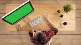 逗人喜爱的妇女谈话在电话,当研究计算机时 绿色屏幕大模型显示 股票视频