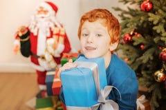 逗人喜爱的姜男孩拥抱圣诞节礼物紧紧 免版税图库摄影