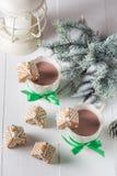 逗人喜爱的姜饼村庄用热巧克力在圣诞节冬天晚上 免版税库存图片