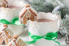 逗人喜爱的姜饼村庄用热巧克力在圣诞节晚上 免版税库存图片