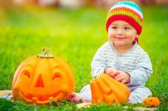逗人喜爱的婴孩用万圣夜南瓜 免版税图库摄影