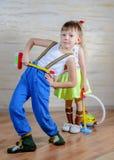 逗人喜爱的嬉戏的小男孩和女孩清洁房子 免版税库存照片