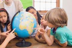逗人喜爱的学生和老师在有地球的教室 免版税库存图片