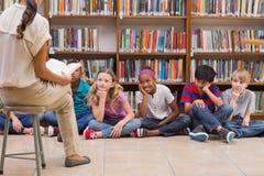 逗人喜爱的学生和老师有类在图书馆 免版税库存照片