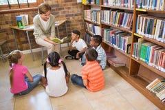 逗人喜爱的学生和老师有类在图书馆 库存照片