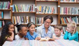 逗人喜爱的学生和老师读书在图书馆里 库存照片