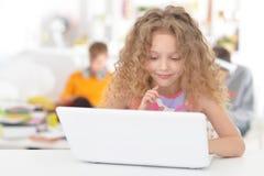 逗人喜爱的学生女孩画象有膝上型计算机的 图库摄影