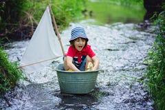 逗人喜爱的孩子、男孩,使用与小船和鸭子在一点劈裂 免版税图库摄影
