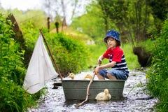 逗人喜爱的孩子、男孩,使用与小船和鸭子在一点劈裂 图库摄影