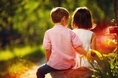 逗人喜爱的孩子一起坐长凳在晴朗的春天庭院里 免版税库存照片