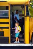 逗人喜爱的孩子上公共汽车,准备上学 免版税库存图片