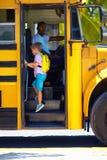 逗人喜爱的孩子上公共汽车,准备上学 图库摄影