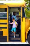逗人喜爱的孩子上公共汽车,准备上学 免版税图库摄影