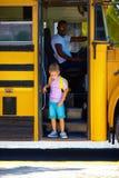 逗人喜爱的孩子上公共汽车,准备上学 库存图片