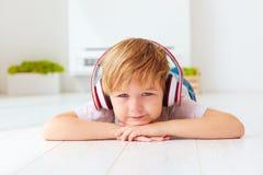 逗人喜爱的孩子听到音乐,在家放松 免版税库存图片