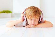 逗人喜爱的孩子听到音乐,在家放松 免版税库存照片