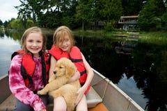 逗人喜爱的孩子和在湖的一只小狗 免版税库存图片