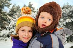 逗人喜爱的孩子在冬天森林里 免版税库存照片