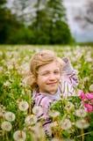 逗人喜爱的孩子在开花的蒲公英花草甸 库存图片