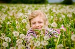 逗人喜爱的孩子在开花的蒲公英花草甸 免版税库存图片