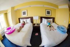 逗人喜爱的孩子在旅馆客房,当乐趣家庭度假时 库存图片