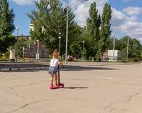 逗人喜爱的孩子在s的一辆桃红色单轮滑行车熟练地滑冰 库存照片