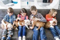 逗人喜爱的孩子坐有小狗英国牛头犬的长沙发 库存照片