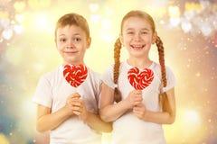 逗人喜爱的孩子小男孩和女孩有糖果红色棒棒糖的在心脏塑造 华伦泰` s天艺术画象 免版税库存图片