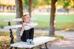 逗人喜爱的孩子开会在想法丢失了美好的秋天天户外 长凳的小女孩在秋天 库存图片