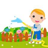 逗人喜爱的孩子浇灌的花 免版税图库摄影