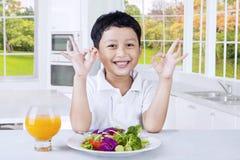 逗人喜爱的孩子用新鲜的沙拉显示好标志 库存照片