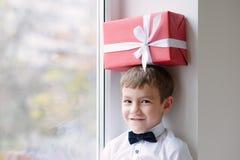 逗人喜爱的孩子由与礼物盒的窗口坐头 免版税库存图片