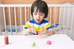 逗人喜爱的孩子由playdough蜘蛛做了牙签腿 库存图片