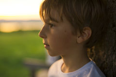 逗人喜爱的孩子的夏天喜悦在后面照的日落 免版税图库摄影