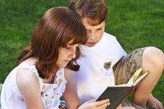 逗人喜爱的孩子阅读书Students.Portrait在自然的包围 免版税图库摄影