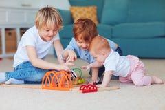 逗人喜爱的孩子,一起演奏玩具的兄弟姐妹在地毯在家 免版税库存图片