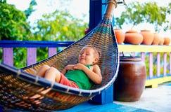 逗人喜爱的孩子,放松在吊床的男孩 享有在热带海岛上的生活 库存照片
