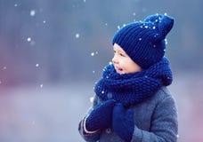 逗人喜爱的孩子,男孩在冬天给使用穿衣在雪下 免版税库存图片