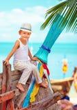 逗人喜爱的孩子,男孩坐在热带海滩的老小船 免版税库存照片