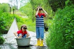 逗人喜爱的孩子,男孩,使用与在一条小的河的小船 免版税库存照片