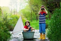 逗人喜爱的孩子,男孩,使用与在一条小的河的小船 免版税图库摄影